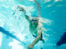 Senior man swimming laps, underwater view stock photography