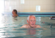 Senior man in swimming pool stock photography