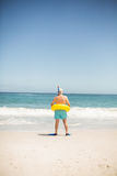 Senior man with swimming ring and flippers at the beach. Senioro man with swimming ring and flippers at the beach on a sunny day Royalty Free Stock Photo