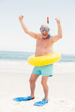 Senior man with swimming ring and flippers at the beach. On a sunny day Royalty Free Stock Image