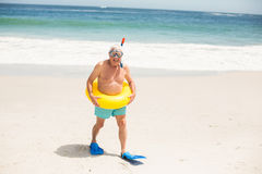 Senior man with swimming ring and flippers at the beach. On a sunny day Royalty Free Stock Images