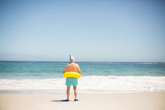 Senior man with swimming ring and flippers at the beach. On a sunny day Stock Photos