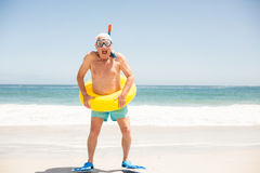 Senior man with swimming ring and flippers at the beach. On a sunny day Stock Photo