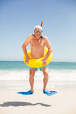 Senior man with swimming ring and flippers jumping. On a sunny day Royalty Free Stock Photography