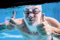 Senior man swimming in an indoor swimming pool. Senior man swimming underwater in an indoor swimming pool. Active pensioner enjoying sport. Thumbs up gesture Stock Photo