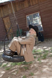 Senior man Swinging on a Tire Swing. A senior man in a western style suit and hat is laughing and swinging on a tire swing. Vertical shot Royalty Free Stock Photo