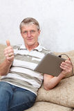 Senior man with tablet device.  Thumb is up Royalty Free Stock Photo