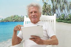 Senior man with tablet on holidays Royalty Free Stock Image