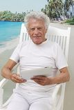 Senior man with tablet on holidays Royalty Free Stock Photography