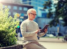 Senior man with tablet pc on city street royalty free stock photo