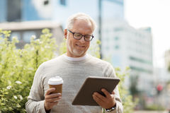 Senior man with tablet pc and coffee in city Stock Photos