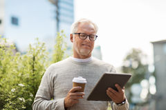 Senior man with tablet pc and coffee in city Stock Image