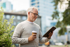 Senior man with tablet pc and coffee in city Stock Photo