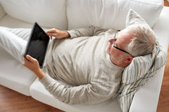 Senior man with tablet pc lying on sofa at home Royalty Free Stock Image
