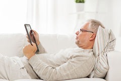 Senior man with tablet pc lying on sofa at home Stock Photography