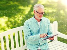 Senior man with tablet pc at summer park royalty free stock image