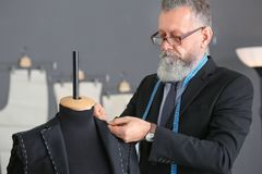 Senior man tailoring formal suit. In atelier Stock Photos