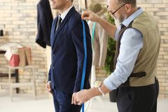 Senior man tailoring sleeve of formal suit. Senior men tailoring sleeve of formal suit in atelier Royalty Free Stock Photography