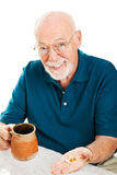 Senior Man Takes Supplements. Senior man taking his vitamins, supplemants, and/or medicine.  White background Royalty Free Stock Photos