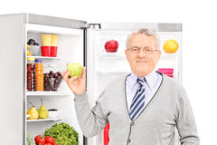 Senior man taking apple out of the refrigerator Stock Image