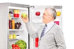 Senior man taking an apple from a refrigerator Royalty Free Stock Photos
