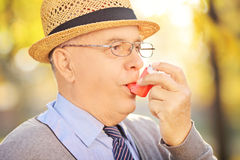 Senior man taking asthma treatment in a park stock photography