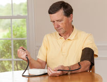 Senior man taking blood pressure at home Royalty Free Stock Images