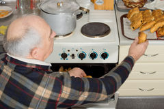 Senior man taking a bread roll out of the oven Royalty Free Stock Images
