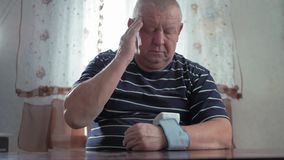 Senior man taking his blood pressure at home on the table. Men health check blood pressure.and heart rate with digital. Pressure gauge standard blood pressure stock footage