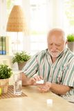 Senior man taking medication at home. Senior man sitting at table, taking medication with glass of water at home Royalty Free Stock Photography