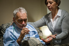 Senior man taking medication with water Stock Photography