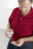 Senior man taking medicine. Senior man holding pills. Vertical shape, side view, waist up Royalty Free Stock Photography