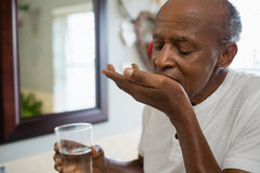 Senior man taking medicine in bathroom. At home Royalty Free Stock Photography