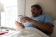 Senior man taking medicine in bedroom. At home Royalty Free Stock Photos