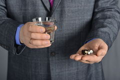 A senior man taking medicine with a glass of water. Senior man looking resigned to the pills hi has to take focus on pills Royalty Free Stock Image