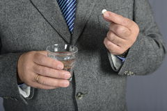A senior man taking medicine with a glass of water. Senior man looking resigned to the pills hi has to take focus on pills Royalty Free Stock Photography