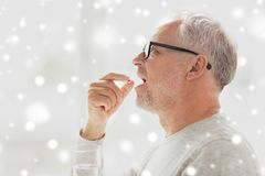 Senior man taking medicine pill at home. Age, medicine, health care and people concept - senior man taking pill at home over snow Stock Photo