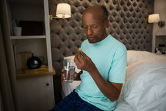 Senior man taking medicine while sitting on bed. At home Royalty Free Stock Photography