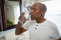 Senior man taking medicine while standing in bathroom. At home Stock Image