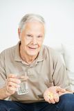 Senior man taking medicine with water Stock Photography