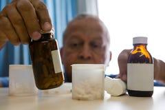 Senior man taking medicines in retirement home. Senior man taking medicines at table in retirement home Stock Photo