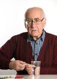 Senior man taking pills Royalty Free Stock Images