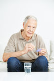 Senior man taking pills out of container Royalty Free Stock Photo