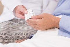 Senior man taking prescribed medicines Royalty Free Stock Photos