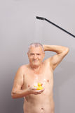 Senior man taking a shower and holding rubber duck. Vertical shot of a senior man taking a shower and holding a yellow rubber duck Royalty Free Stock Images