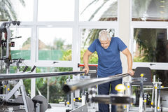 Senior Man Taking Support Of Bars At Rehab Center. Senior man taking support of bars while walking in fitness studio at rehab center Stock Images