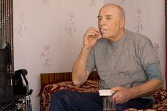 Senior man taking a tablet and his blood pressure Royalty Free Stock Images