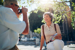 Senior man taking vacation photograph of his wife Royalty Free Stock Photography