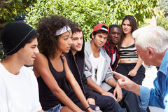 Senior Man Talking With Gang Of Young People. Pointing To Female royalty free stock images