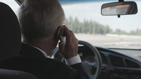 Senior Man is talking on the mobile phone in the car stock video footage